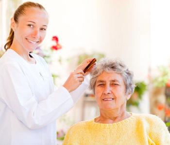 caregiver combing the hair of elder woman